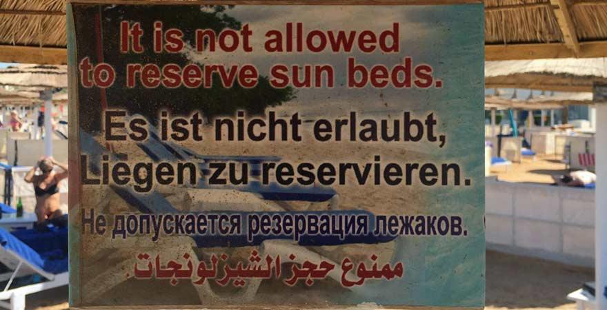 """Schild am Strand in Ägypten: """"Liegen reservieren verboten!"""""""