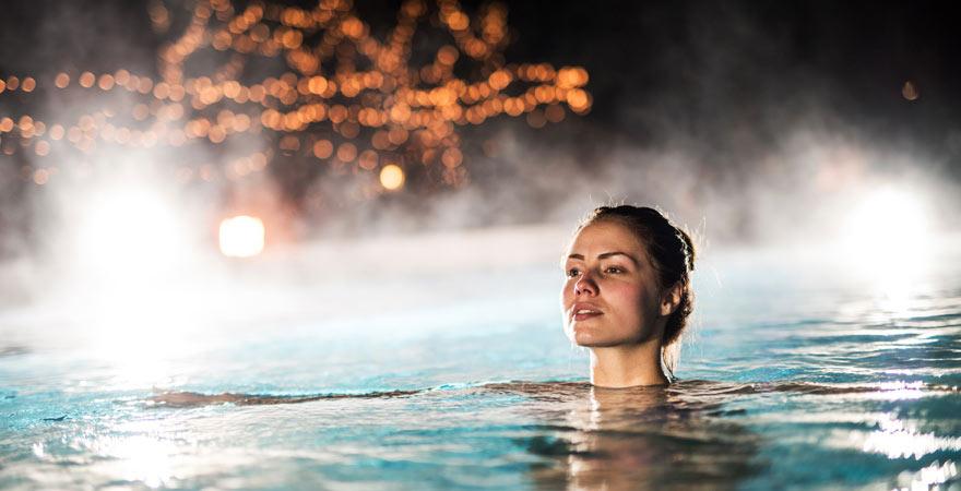 Frau schwimmt im beheizten Pool einer Therme
