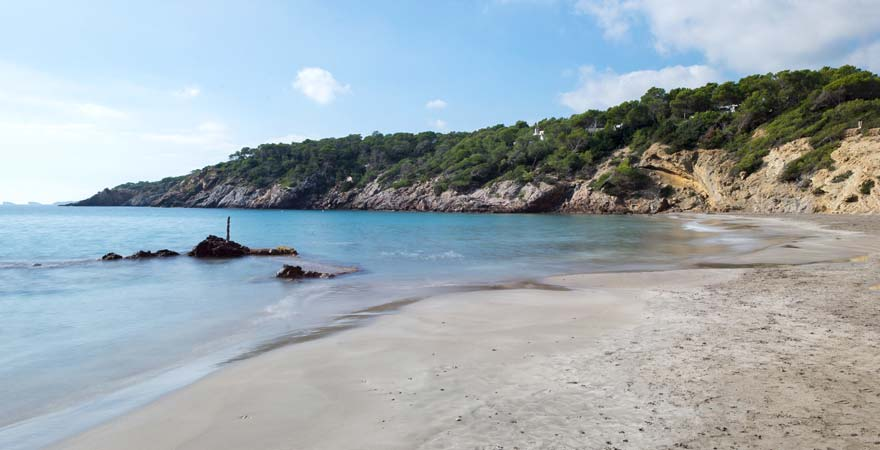 Der dunkle Strand von Cala Boix bildet einen schönen Kontrast zum Meer und zählt damit zu den schönsten Stränden Ibizas