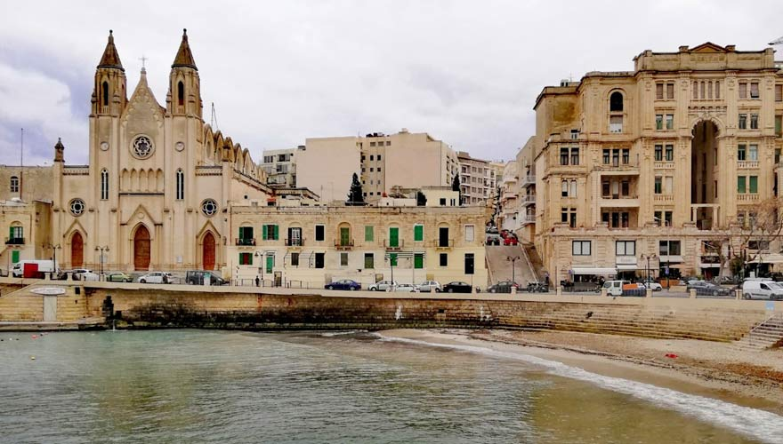 Schmaler Kieselstrand von der Balluta Bay vor der Kulisse von St. Julian's auf Malta