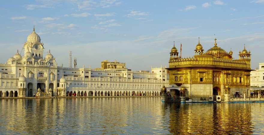 Die Fassade des Goldenen Tempels in Amritsar in Indien speigelt sich im Wasser eines Sees
