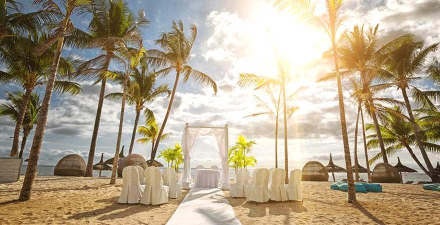 Ein weißer Baldachin und weiße Stühle am Strand auf Mauritius