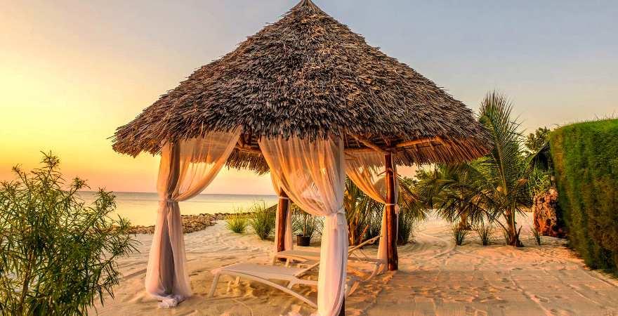 Pavillon mit dach aus Palmblättern im Abendlicht am Strand von Sansibar