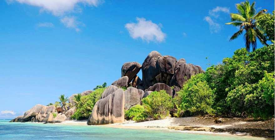 Weißer Sandstrand mit Felsen und Palmen auf La Digue, Seychellen