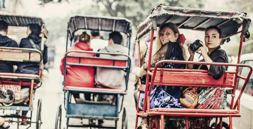 Zwei Frauen erkunden in einer Riksha eine indische Stadt