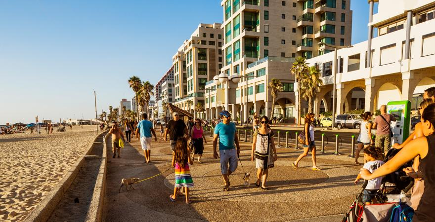 Einwohner und Touristen gehen an der Promenade am Strand von Tel-Aviv in Israel spazieren