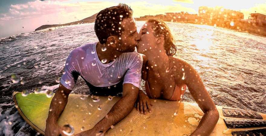 Ein küssendes Pärchen schwimmt auf einem Surfbrett im Meer