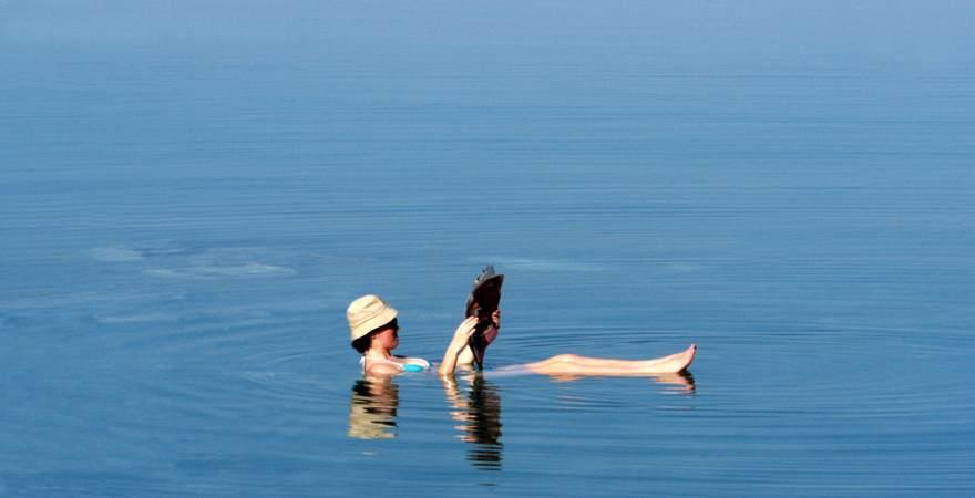 Eine Frau schwimmt im Toten Meer in Israel und liest dabei Zeitung