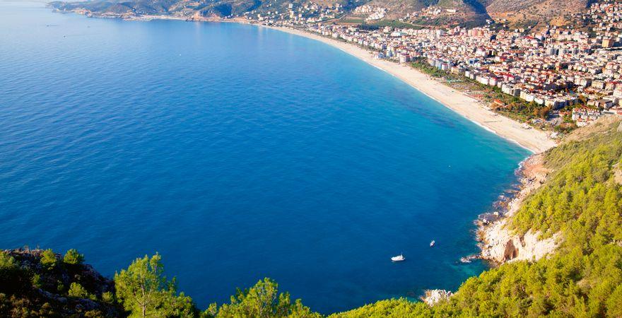 Der Kleopatra Strand bei Alanya in der Türkei mit Blick vom grünen Hügel auf Meer, Sand und Stadt