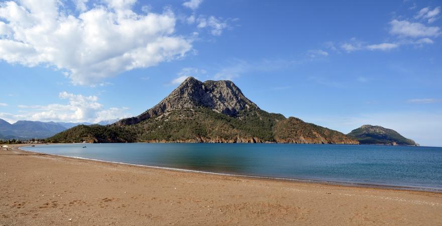 Der Sand-Strand Adrasan in der Türkei mit Blick auf das blaue Meer und einen grünen Hügel