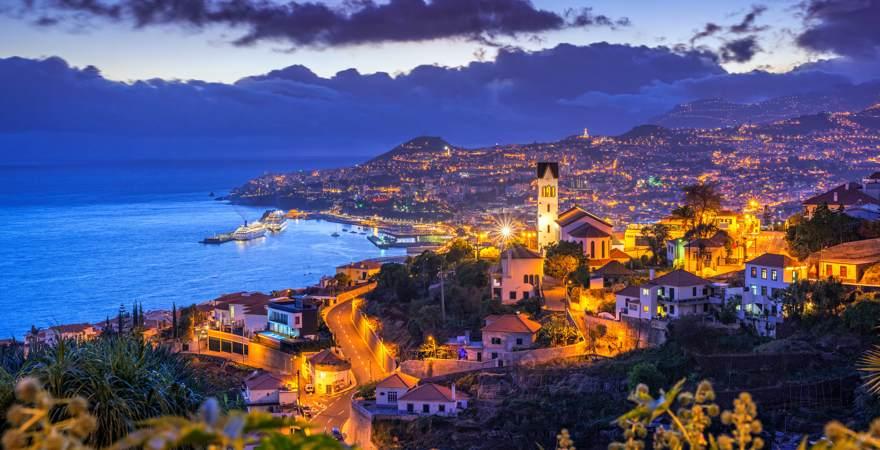 Madeiras Hauptstadt Funchal bei Nacht mit Meer und Bergen