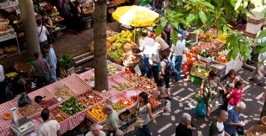 Einheimische und Touristen spazieren über denMarkt von Funchal auf Madeira auf dem Obst, Gemüse und Blumen angeboten ewrden