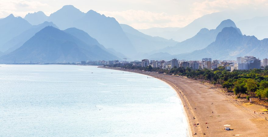 Der Konyaalti Strand in der Türkei mit Blick auf das Meer, Kiesstrand mit Sand, Wald und Bergen