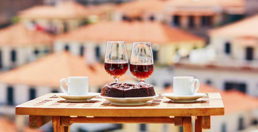 Zwei Gläser mit Madeira Wein, Kaffee und der Honigkuchen Bolo de Miel mit Funchal Hauptstadt von Madeira im Hintergrund