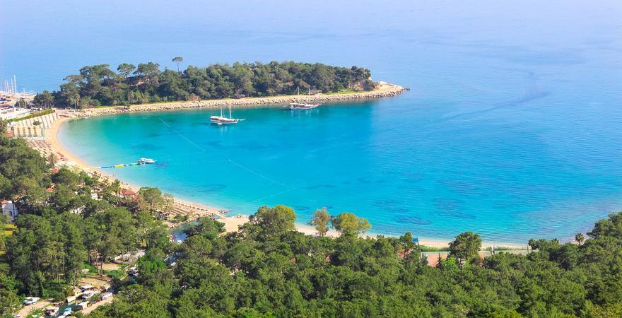 Der Moonlight Strand bei Kemer in der Türkei liegt in einer Bucht mit weißem Sandstrand und grünem Wald