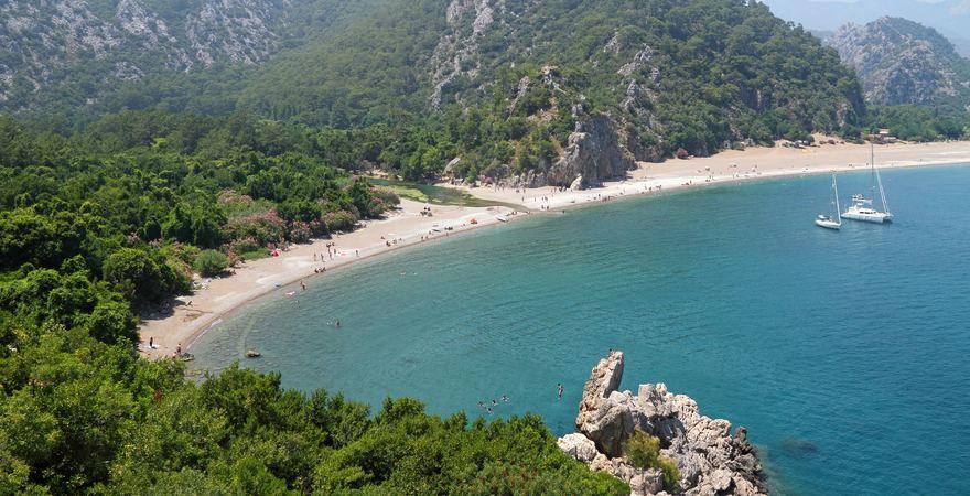 Der Strand Olympos vor dem Taurusgebirge in der Türkei mit Blick auf grüne Berglandschaft, Wald, Kiesstrand und Meer