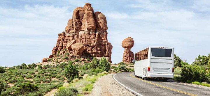 Ein Reisebus auf einer Straße vor roten Felsen