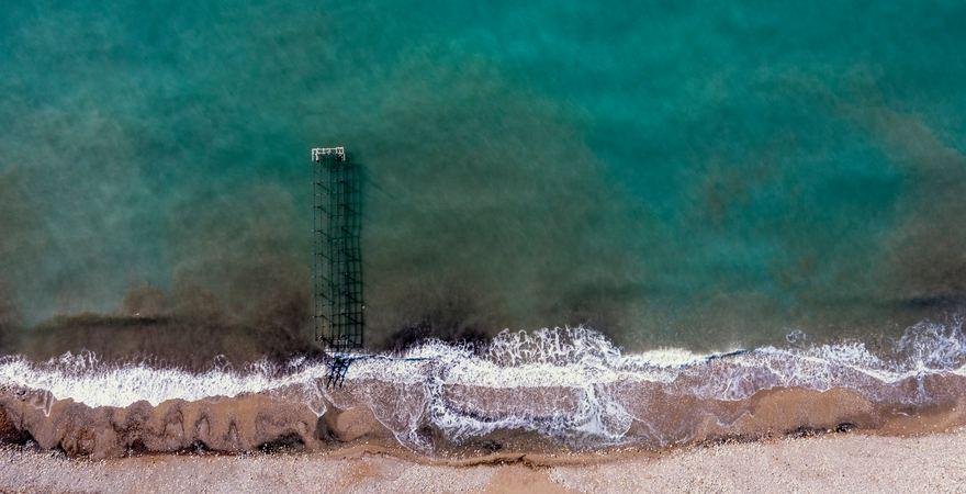 Ein Pier vor dem Lara Strand in der Türkei in Antalya mit Sand und Kies der ins Meer hineinragt und von Wellen umspült wird